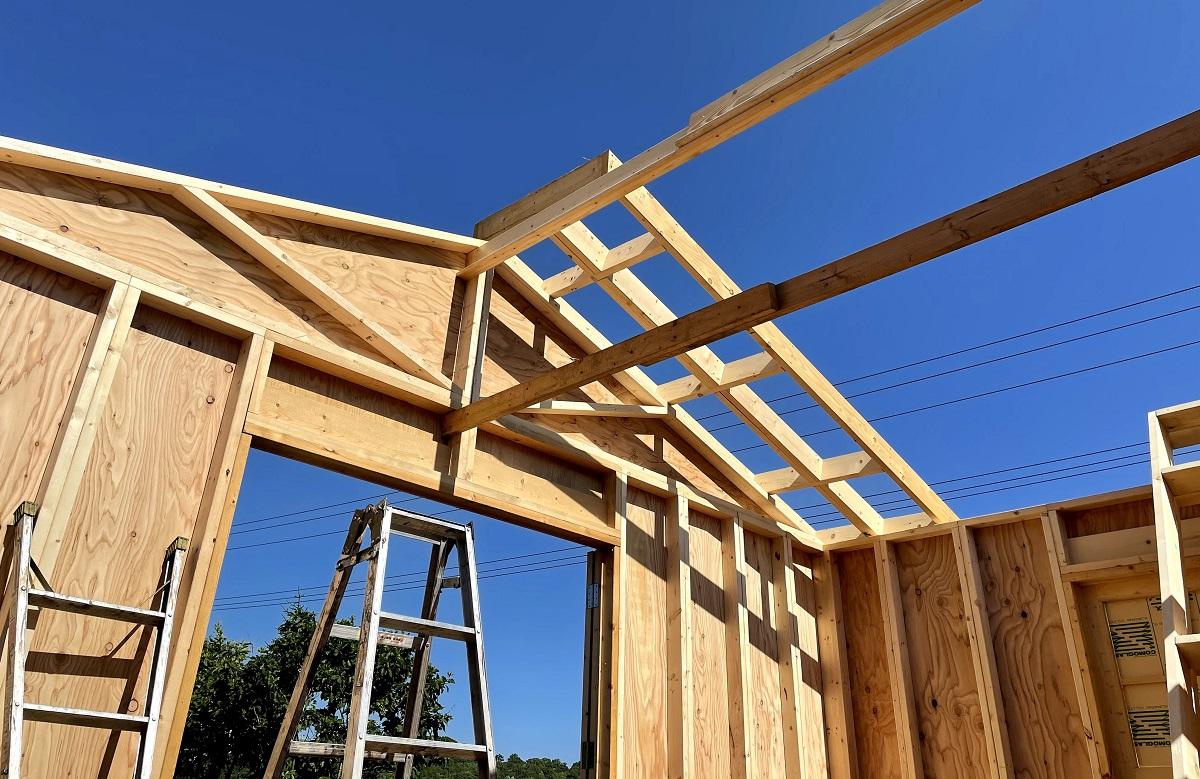 高い壁の上で屋根パネルを左右1組作って、少しずつずらし1組ずつ合わせていく地味な作業